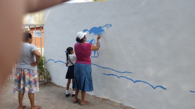 Noemi and her mother, Doña Celia, painting her mural