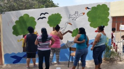 Members of a local environmental group, Women for a clean Boca de Camichin, help paint Yurem´s mural