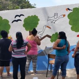 Members of a local environmental group, Women for a clean Boca de Camichin, help paint Yurem´s mural